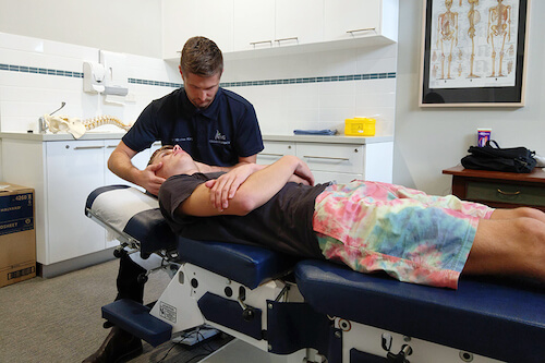 Chiropractor Bunbury Nicolas King doing an assessment and treatment on a young man