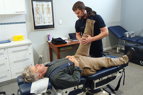 Bunbury Chiropractor from King Chiropractic doing an assessment and treatment of a man laying down on one of their modern chiropractic tables